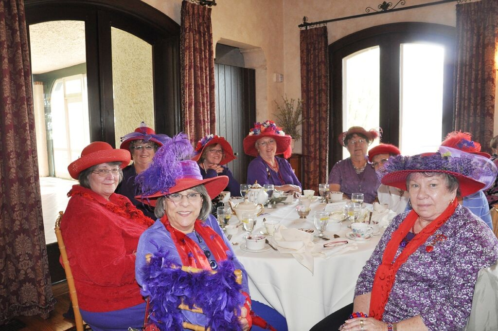 Red Hatter ladies club dining in living room.