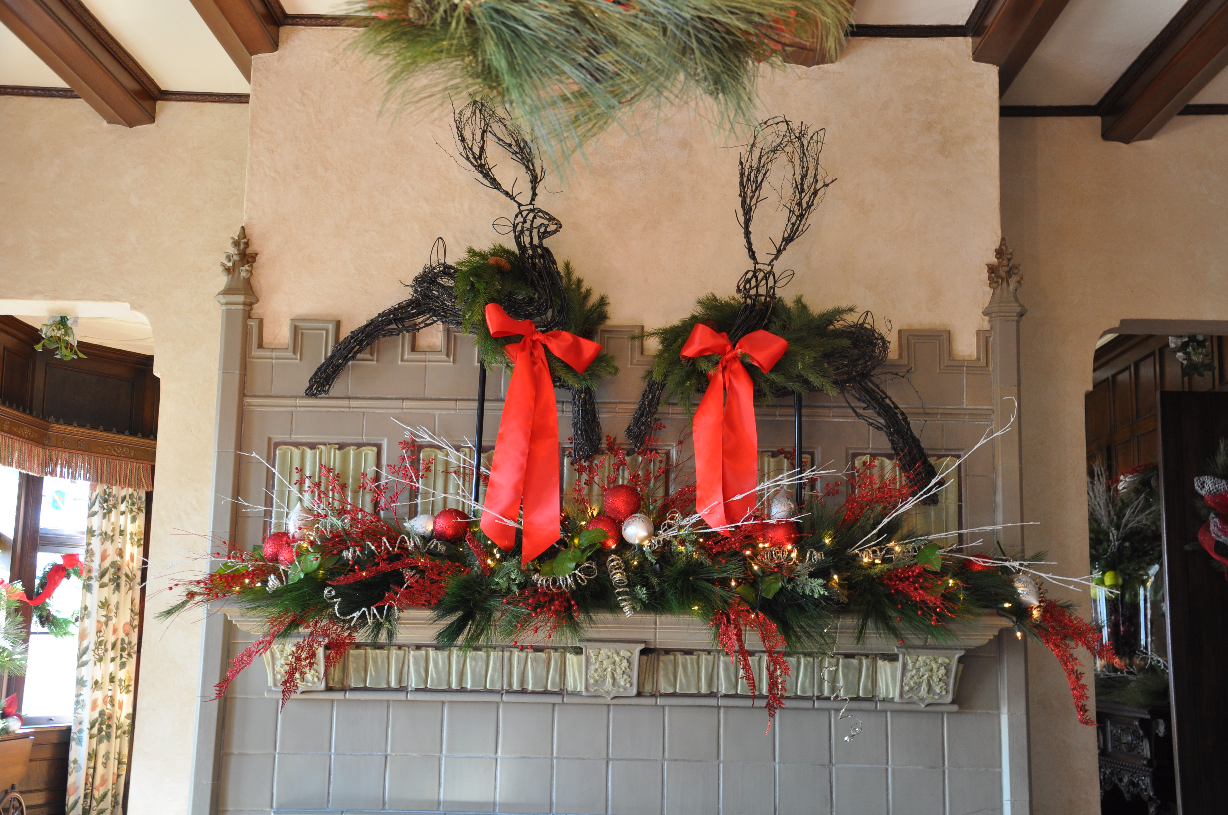HWoliday Walk Mantel dressed ith deer and red decor