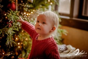 Child in front of Christmas tree in the living room of the Kellogg Manor House