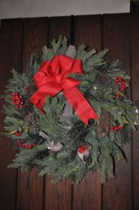 A holiday wreath made of evergreens, red berries, and a red bow hanging on a door