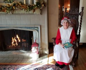 Mrs. Claus seated next to a fire in the Manor House fireplace, holding a book on her lap